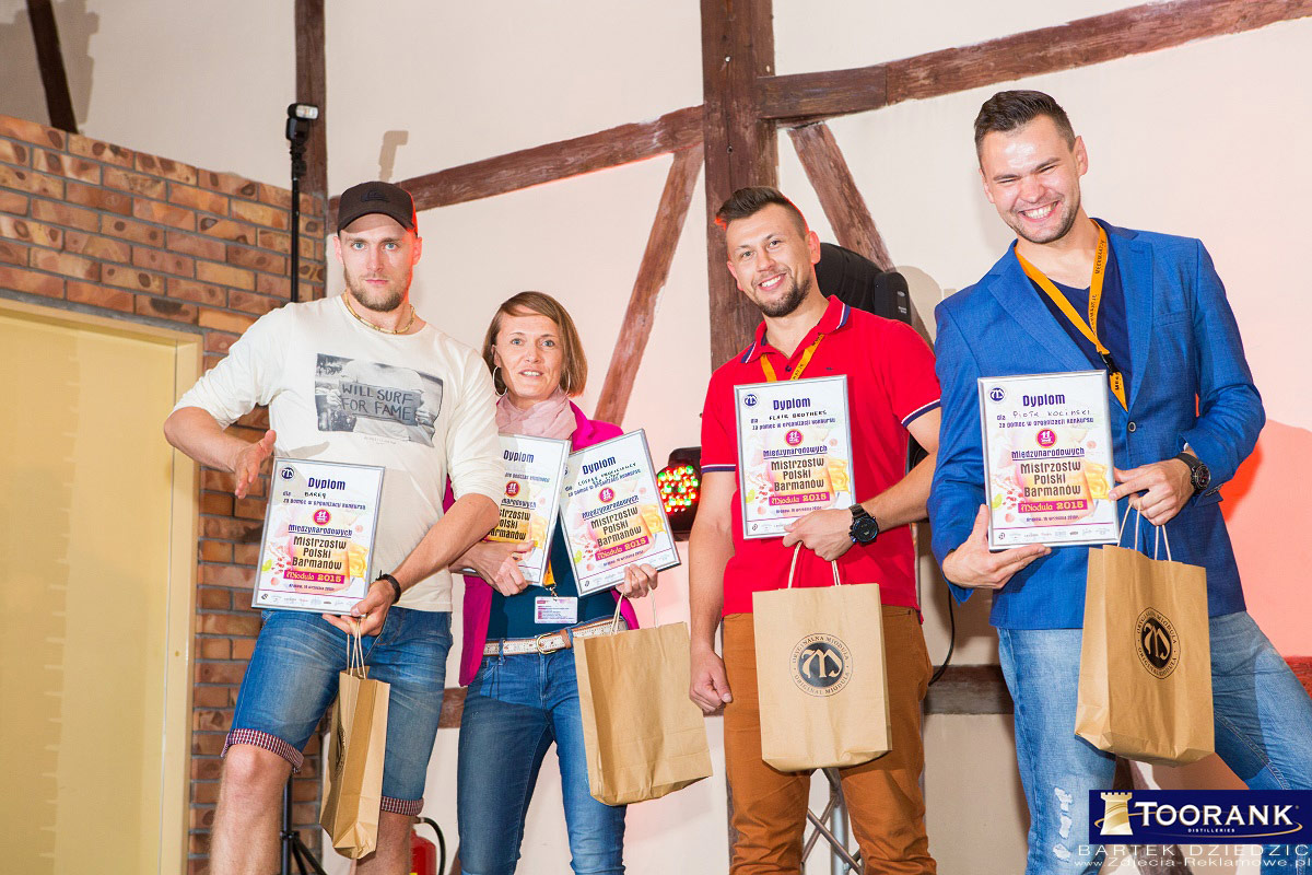 Obsługa imprez firmowych Kraków. Wyróżnione osoby z nagrodami pozują do grupowego zdjęcia.