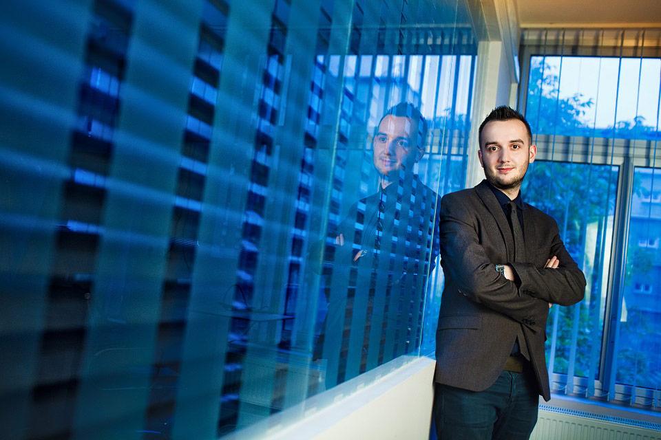 Portret biznesowy wykonany w biurze. Zdjęcie z niebieskim tłem. Profesjonalnie pokazany wizerunek osoby to jedna z lepszych inwestycji na jaką powinien zdecydować się każdy kto szuka pracy, czy chce rozwijać swój własny biznes. Profesjonalne zdjęcia to podstawa.
