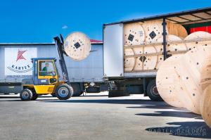 Zdjęcie przedstawia załądunek bębna na samochód ciężarowy.
