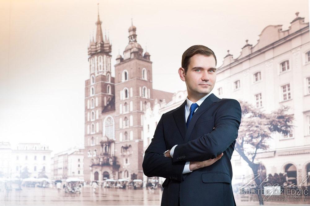 Zdjęcia biznesowe Kraków. Sfotografowano osobę na tle fototapety.