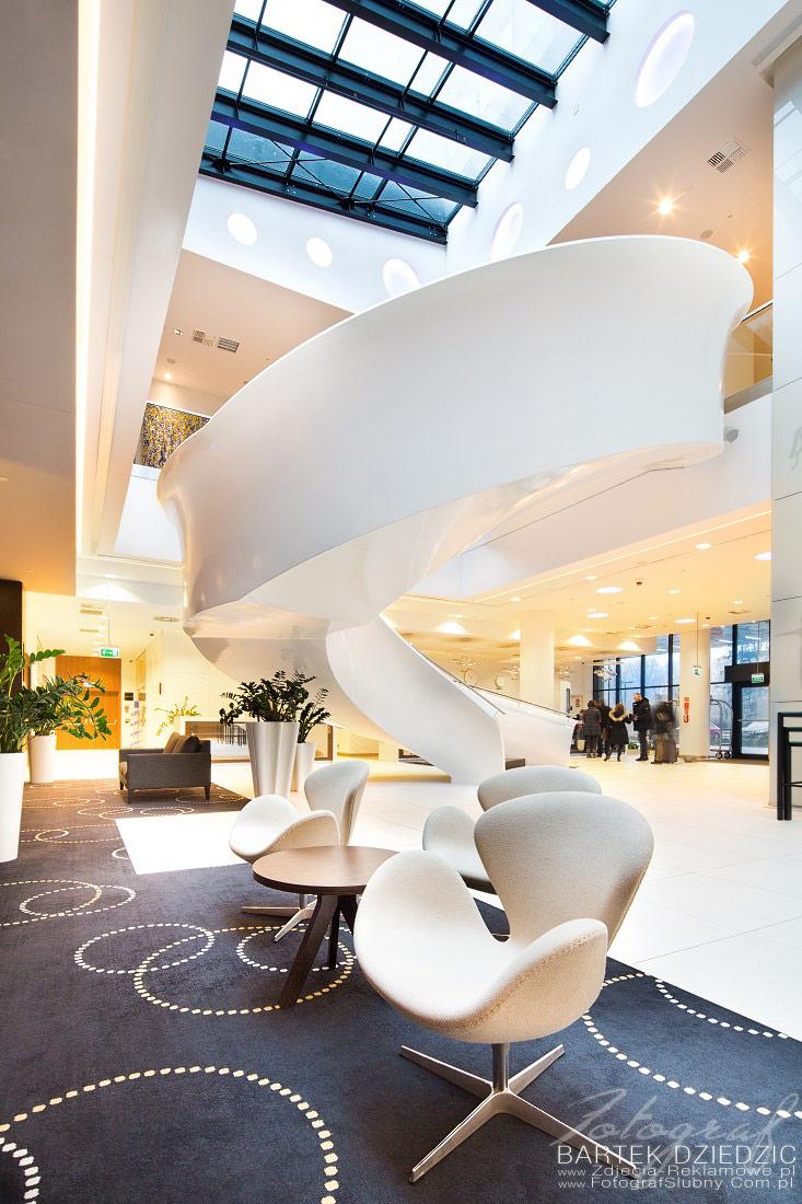Zdjęcia reklamowe Kraków. Na zdjęciu widok wnętrza, lobby, nowoczesne schody oraz w tle recepcja.