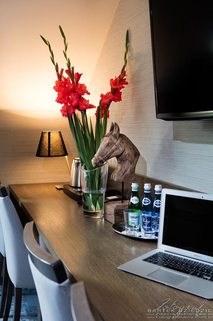 Zdjęcia reklamowe. Na zdjęciu biurko z laptopem, wodą, rzezbą konia, kwiatami w wazonie.